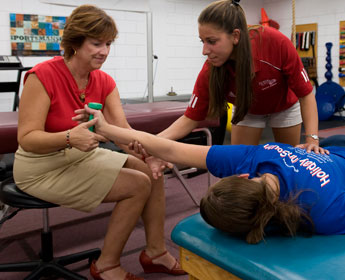 Professor and student working together on a physical therapy exercise.