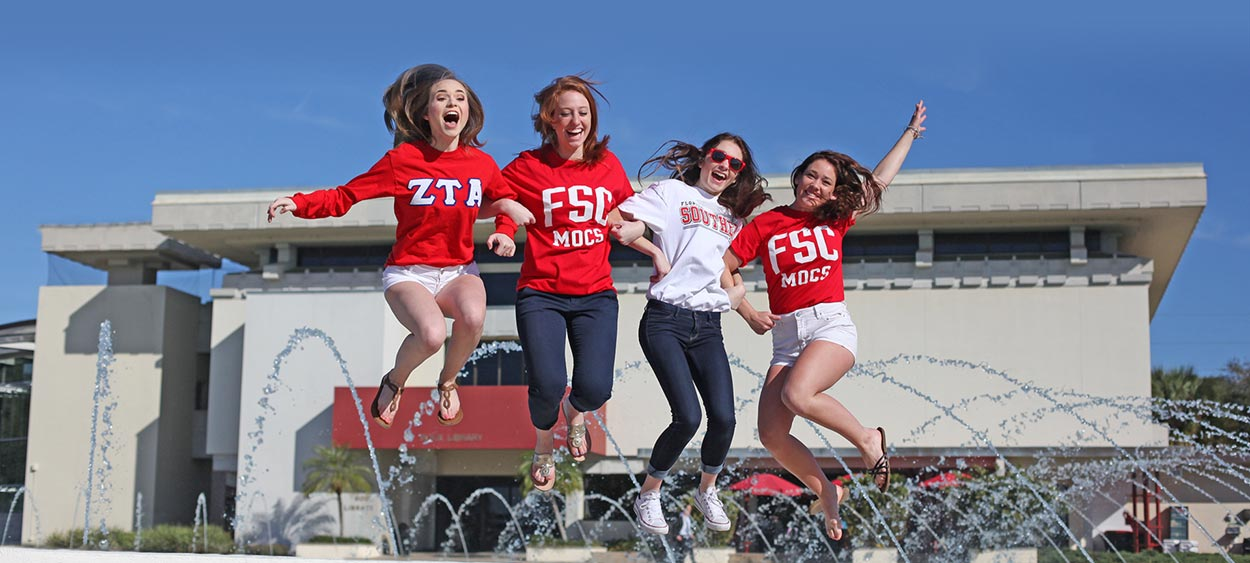 Students jumping for joy in front of the Frank Lloyd Wright Water Dome on a sunny Florida day.
