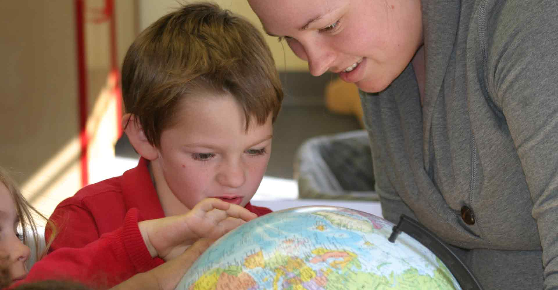 Student working with child on geography with a globe